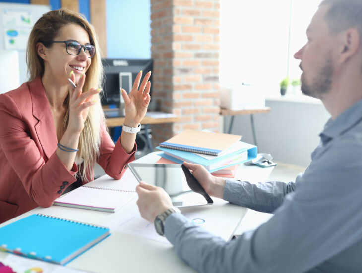 Two adult business people make work interview against office background