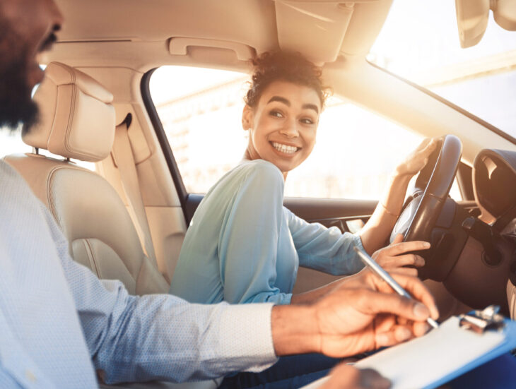 Happy woman in examination car, smiling to male instructor